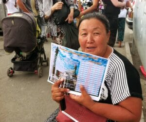"""Woman selling the """"azan"""" schedule at Osh Bazaar, which changes everyday, so Muslims know when to eat breakfast and dinner."""