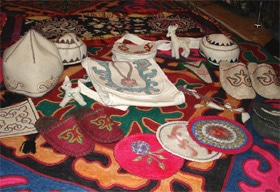 Felt purses, slippers, hats, coasters, and stuffed animals that Rakhat's mother made. On the bottom, you can see the rug that she made for the young couple.