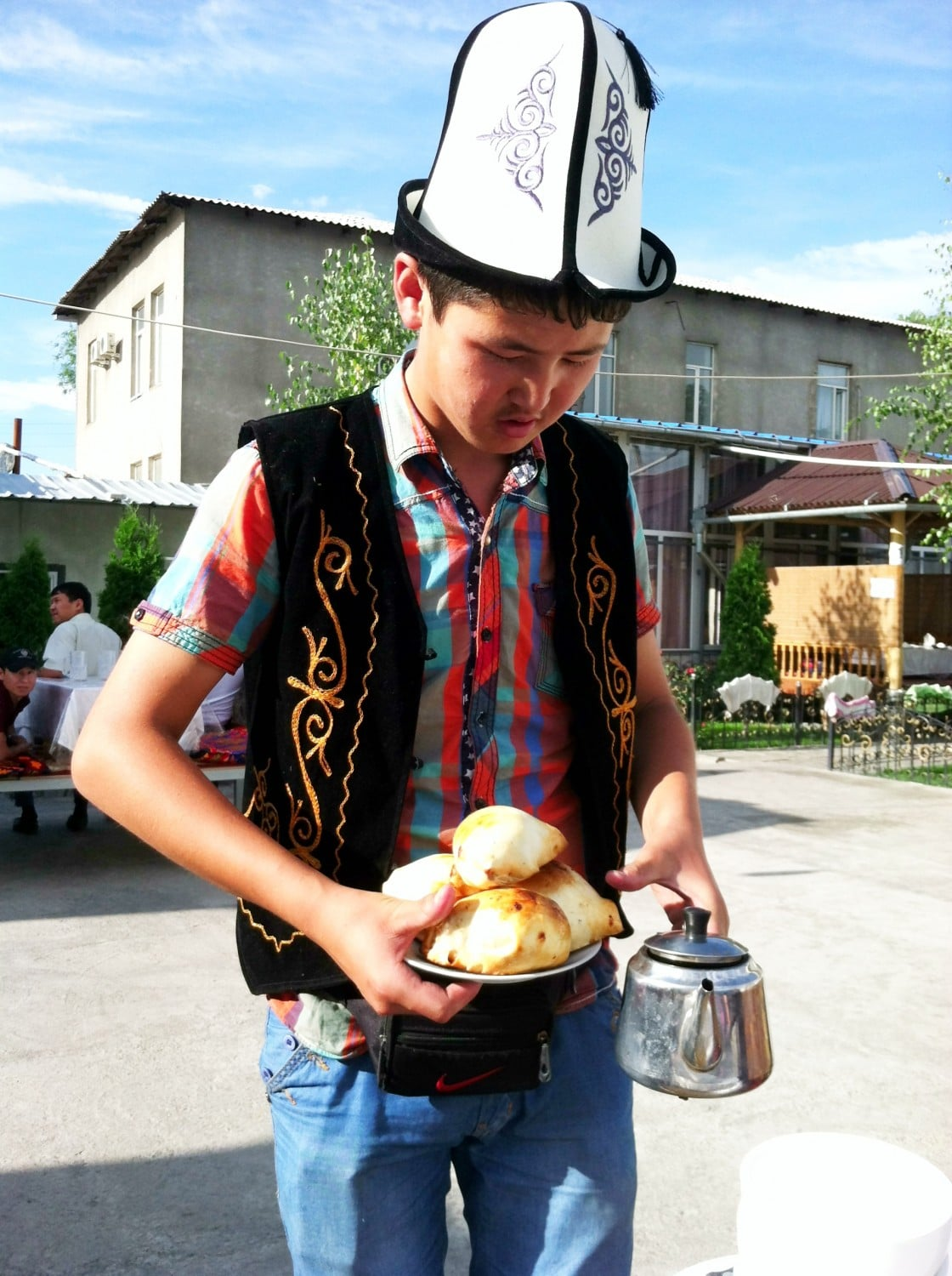 Waiter in a traditional Kyrgyz hat called kalpak serving us spicy and non-spicy samsa